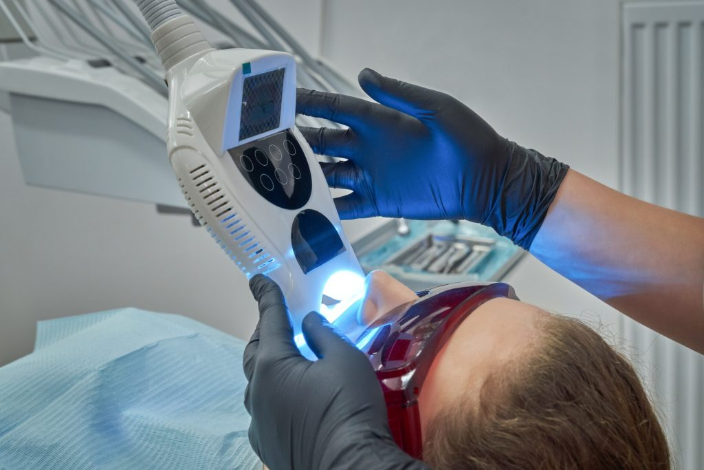 Woman lying on chair during procedure of whitening of teeth